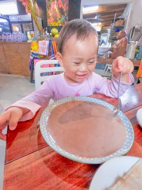 Little Kyra pouring hot chocolate into a plate and happily playing with it