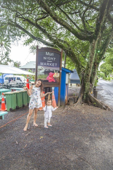 Mommy and daughter shrugging in front of Muri Night Market sign that no one is here on a rainy day and empty stalls