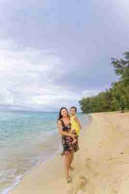 Mommy and daughter walking along the beach at The Rarotongan Beach Resort