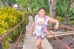 Mom carrying baby in ergo baby carrier on steep steps of top attraction in Apia Samoa