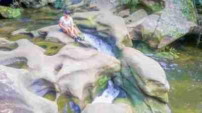Blue Gum Walk Hornsby Waitara Creek Girl sitting on sandstone with stream running beneath her in Blue Gum Walk Hornsby Sydney Australia